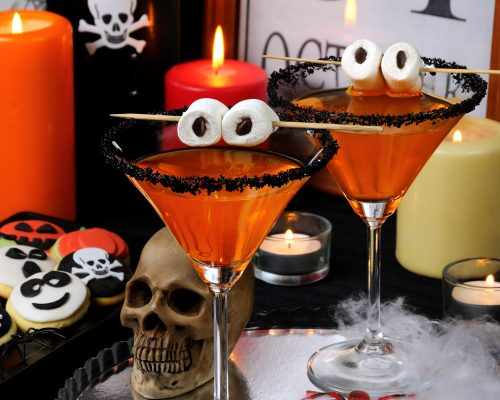 glass of citrus martini decorated with black sugar with marshmallow eyes on the table in honor of Halloween