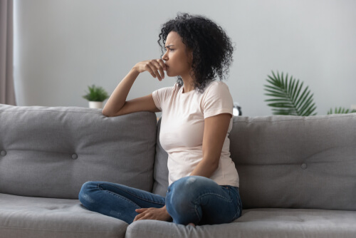 Anxious worried woman sitting on couch looking into the distance